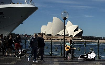 Illustrative: A man plays a song on a guitar on the Sydney Harbor in front of the iconic Opera House on May 11, 2016.  (AFP/SAEED KHAN)
