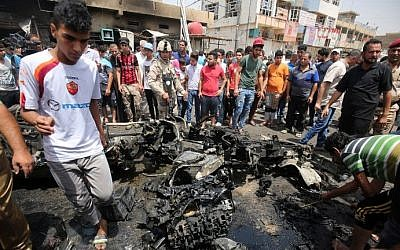 Iraqis check the site of a car bomb attack in Sadr City, a Shiite area north of the capital Baghdad, May 11, 2016.  (AFP/AHMAD AL-RUBAYE)