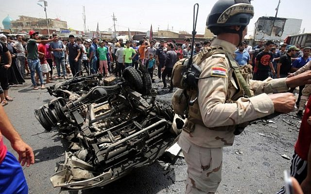 A member of the Iraqi security forces stands guard as civilians look at the damage following a car bomb attack in Sadr City, a Shiite area north of the capital Baghdad, on May 11, 2016. (AFP PHOTO / AHMAD AL-RUBAYE)