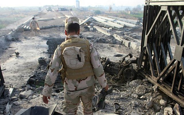 Fighters from Iraqi pro-government forces inspect the damage at the Albu Aitha bridge north of Ramadi following an attack a military source said was carried out by the Islamic State (IS) group, May 12, 2016. (Moadh Al-Dulaimi/AFP)