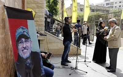 Lebanese press report from outside where family members are receiving condolences for the death of top Hezbollah commander Mustafa Badreddine who was killed in an attack in Syria in a southern suburb of Beirut on May 13, 2016. (AFP PHOTO / ANWAR AMRO)