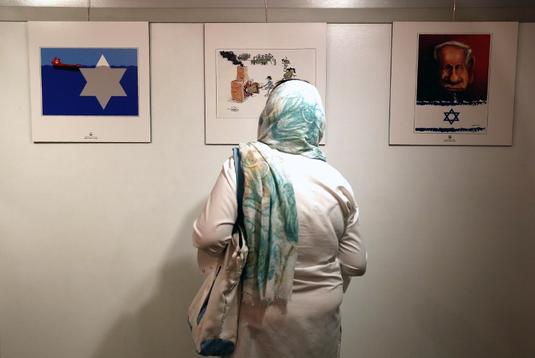 An Iranian woman looks at anti-Israel cartoons displayed at the second international exhibition of drawing and cartoons on the Holocaust in Tehran on May 14, 2016. (AFP PHOTO / ATTA KENARE)