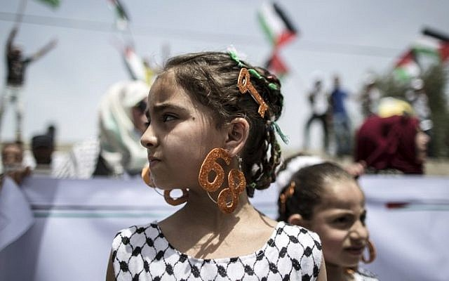 """A Palestinian girl wears earrings bearing the number """"68"""" and a hair slide in the shape of a key on May 15, 2016 in Gaza city during a rally to commemorate the """"Nakba."""" (AFP PHOTO / MAHMUD HAMS)"""
