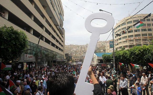 """A Palestinian man carries a key during a rally to commemorate the 68th anniversary of the """"Nakba"""" on May 15, 2016 in the West Bank city of Nablus. (AFP/ JAAFAR ASHTIYEH)"""