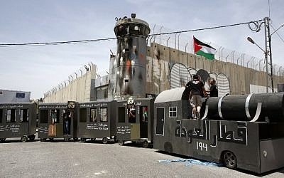 """Palestinians stand on a makeshift train on May 15, 2016 in front of  the Israeli security barrier during  demonstration to mark the """"Nakba."""" (AFP PHOTO / HAZEM BADER)"""