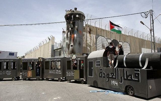 "Palestinians stand on a makeshift train on May 15, 2016 in front of  the Israeli security barrier during  demonstration to mark the ""Nakba."" (AFP PHOTO / HAZEM BADER)"