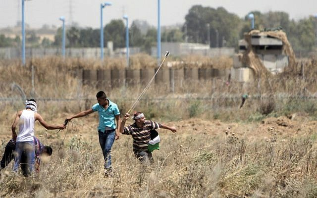 Palestinian youth hurl rocks at Israeli military during clashes at the border east of Gaza city on May 15, 2016, on the 68th anniversary of the 'Nakba.' (AFP/Mahmud Hams)