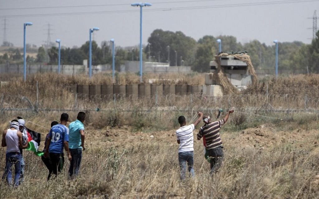 """Palestinian youth hurl rocks at Israeli military during clashes at the border east of Gaza city on May 15, 2016, on the 68th anniversary of the """"Nakba."""" (AFP/MAHMUD HAMS)"""