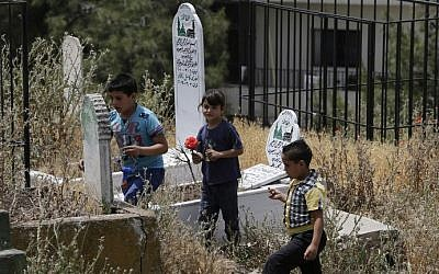 Children place flowers on a tomb in the old cemetery of Bar Elias in Lebanon's Bekaa Valley on May 13, 2016. (AFP PHOTO / JOSEPH EID)