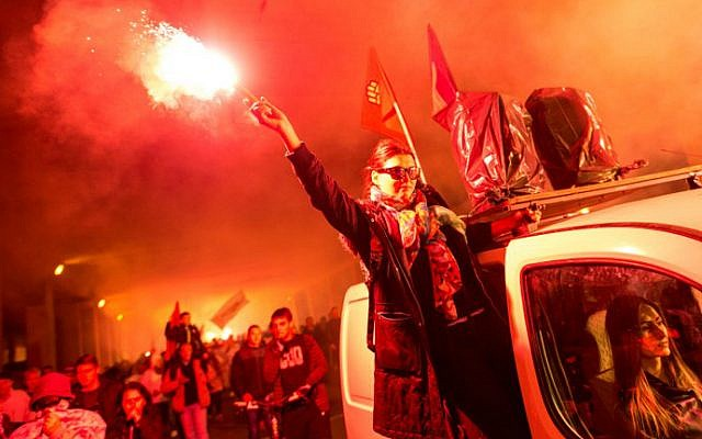 Protesters light flares and wave flags while marching through a street during an anti-government protest in Skopje, Macedonia, on May 16, 2016. (Robert Atanasovski/AFP)