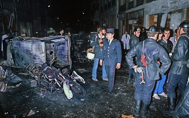 This file photo taken on October 3, 1980 on rue Copernic in Paris shows firemen standing by the wreckage of a car and motocycle after a bombing attack of the rue Copernic synagogue, resulting in the death of four people. (AFP/STF)