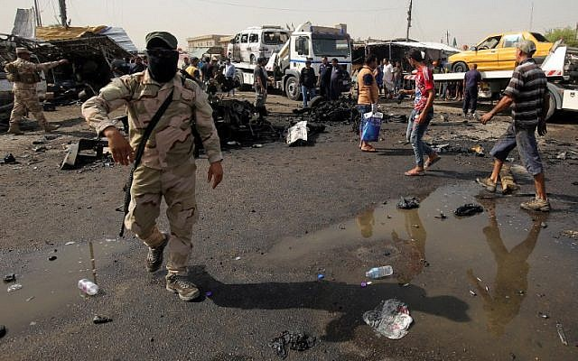 Iraqi soldiers and civilians check the damage after a suicide bomber detonated an explosives-rigged vehicle in northern Baghdad's Sadr City, May 17, 2016. (AFP/AHMAD AL-RUBAYE)