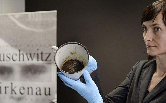 A woman presents on May 19, 2016 a metal mug with a double bottom in which a gold ring and necklace were found by employees of the Auschwitz-Birkenau museum in Oswiecim, Poland. More than 70 years after the liberation of the World War II camp in occupied Poland, staff discovered the jewellery in a rusting enamel mug, one of thousands of pieces of kitchenware now on display at the museum. (Bartosz Siedlik/AFP)