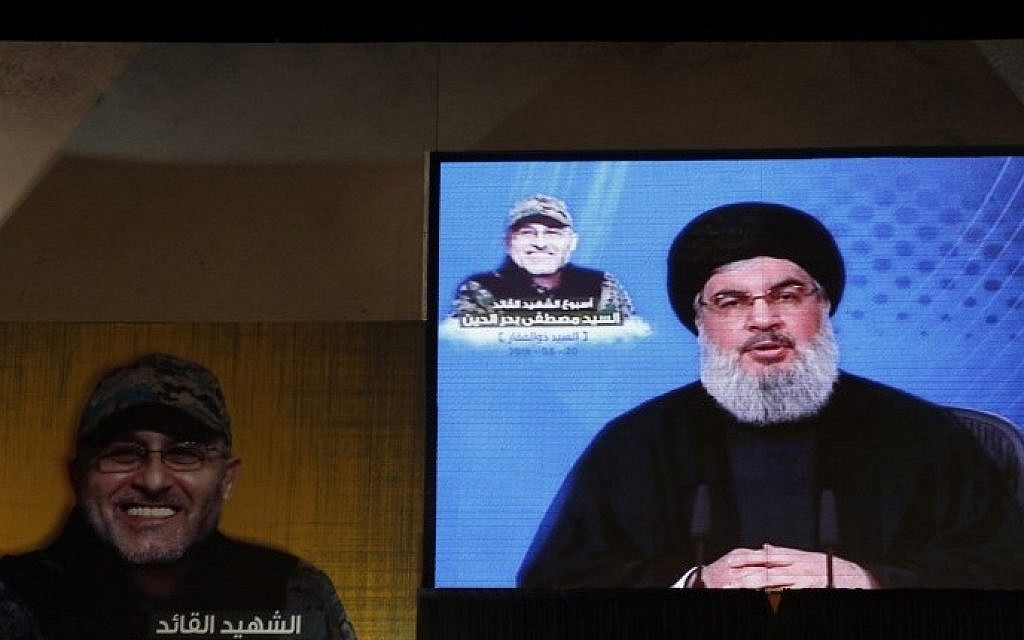 Hezbollah's leader Hassan Nasrallah is seen on a giant screen broadcasting his speech on May 20, 2016 in a southern suburb of the capital Beirut during a memorial ceremony to mark a week since slain Hezbollah commander Mustafa Badreddine (portrait) was killed in an artillery attack near Damascus. (Joseph Eid/AFP)