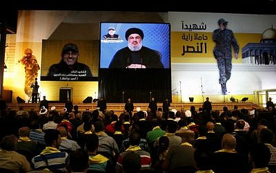 File: Hezbollah leader Hassan Nasrallah in a video broadcast on May 20, 2016 in a southern suburb of the capital Beirut during a memorial ceremony to mark a week since slain Hezbollah commander Mustafa Badreddine (portrait) was killed in an explosion near Damascus. (Joseph Eid/AFP)
