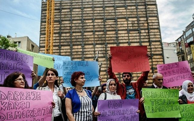 """Supporters of People's Democratic Party (HDP) hold placards reading """"We do not accept palace's coup - Democratic resists agianst palace's coup"""" on May 20, 2016 during a protest at the Istiklal avenue in Istanbul. (AFP PHOTO / OZAN KOSE)"""