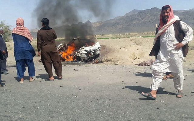 Pakistani local residents gathering around a destroyed vehicle hit by a drone strike in which Afghan Taliban Chief Mullah Akhtar Mansour was believed to be travelling in the remote town of Ahmad Wal in Balochistan,  May 21, 2016. (AFP)