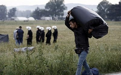 A refugee man carries his belongings during an evacuation operation by police forces of a makeshift migrant camp at the border at the Greek-Macedonian border near the village of Idomeni, on May 24, 2016. (AFP PHOTO / POOL / Yannis KOLESIDIS)