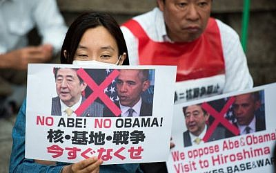 Protesters hold posters reading 'No Abe! No Obama! -- We oppose Abe and Obama visit to Hiroshima' during a demonstration next to the Hiroshima Peace Memorial park in Hiroshima on May 26, 2016. (AFP/Johannes Eisele)