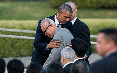 US President Barack Obama hugs a survivor of the atomic bombing of Hiroshima at the Hiroshima Peace Memorial park cenotaph in Hiroshima on May 27, 2016. (AFP Photo/Johannes Eisele)