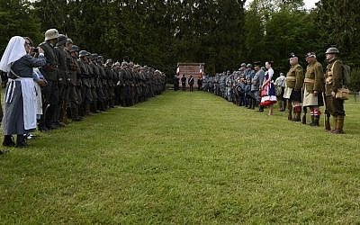 Reenactors dressed as French and German soldiers take part in a ceremony at the German World War I cemetery of Troyon, eastern France, on May 28, 2016, as part of the 100-year commemoration of WWI's Battle of Verdun. (AFP/Jean-Christophe Verhaegen)