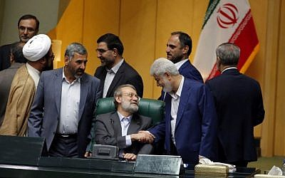 Iran's re-elected Parliament speaker Ali Larijani (C) is congratulated by MPs following the announcement of the results during a parliament session in Tehran on May 29, 2016. (AFP PHOTO / ATTA KENARE)