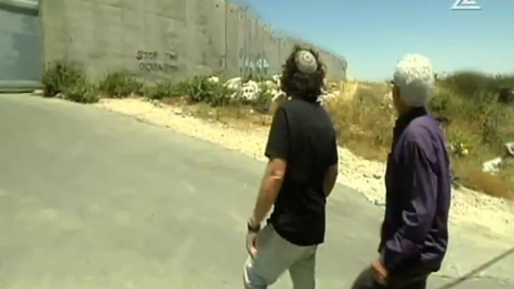 Eliaz Cohen and Muhammad Beiruti, members of the Two States, One Homeland movement, walking toward the security fence that separates the West Bank and Israel. (Screen capture Channel 2)