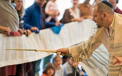 Rabbi Amichai Lau-Lavie chants as members of the Lab/Shul community hold an unfurled Torah scroll. (Courtesy)