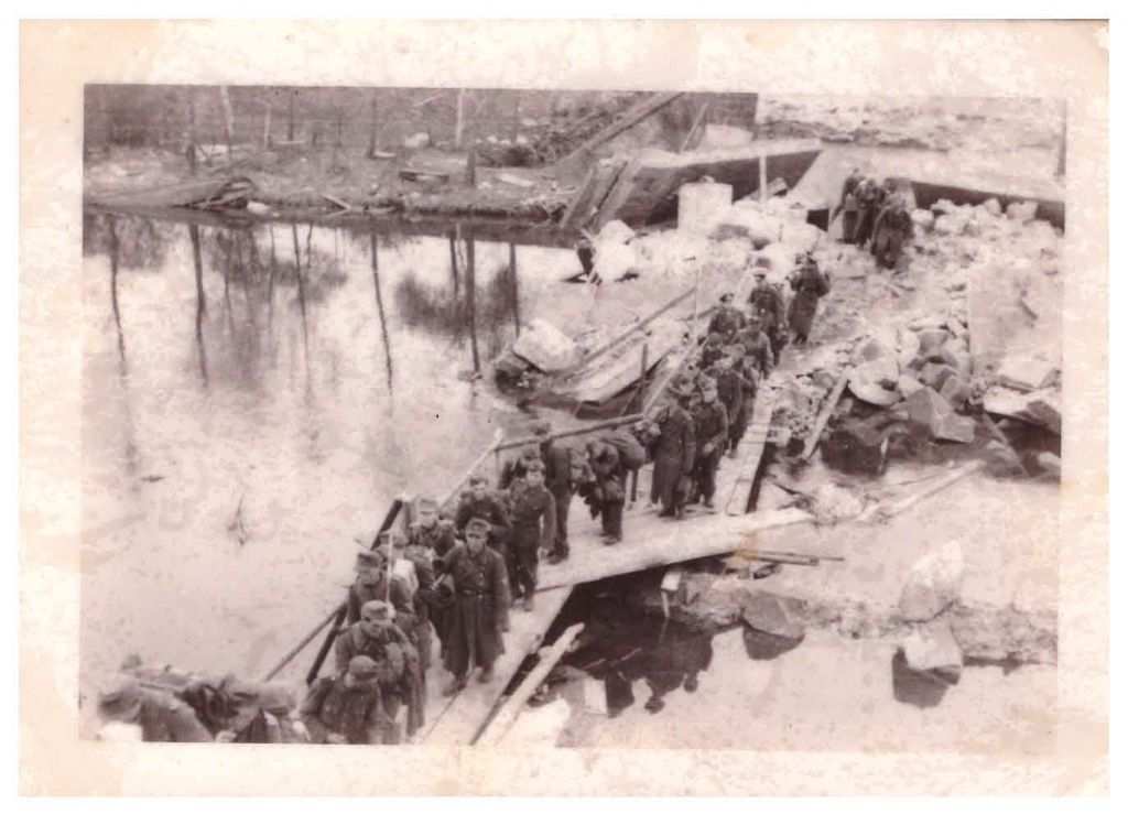 """German prisoners of war crossing the Mulde River on an improvised pontoon bridge. These Nazis chose to give up to the 104th US Inf. Div. rather than give up to the Russians."" April 1945, near Bitterfeld, Germany. (Jules Helfner)"