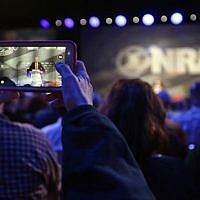 A National Rifle Association attendee photographs Republican presidential candidate Donald Trump as he speaks at the NRA convention, Friday, May 20, 2016, in Louisville, Ky. (AP Photo/Mark Humphrey)