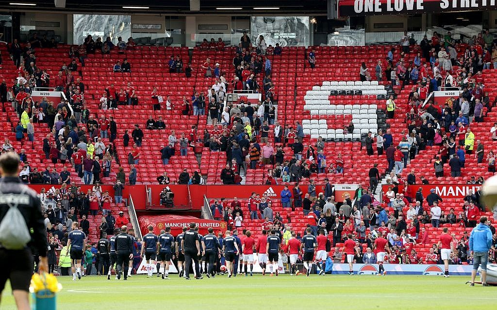 Fans leave the stands after an English Premier League match at Old Trafford, Manchester, England was called off Sunday May 15, 2016 over a security threat (Martin Rickett/PA via AP)