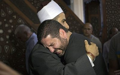 The Imam of al Thawrah Mosque, Samir Abdel Bary, embraces film director Osman Abu Laban, center, who lost four relatives in Thursday's EgyptAir plane crash, following prayers for the dead at the Cairo mosque on May 20, 2016. (Amr Nabil/AP)