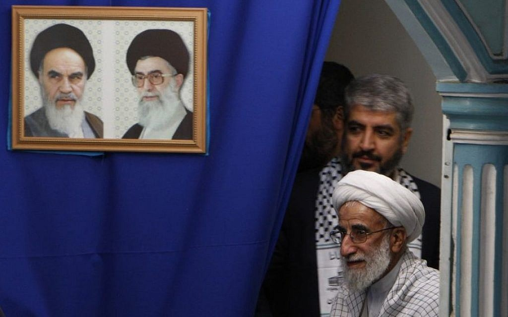 Ayatollah Ahmad Jannati arrives with Hamas chief Khaled Mashaal at a ceremony at Tehran university, Feb. 2, 2009. The picture frame features Iran's late leader Ayatollah Khomeini, left, and Iran's supreme leader Ayatollah Ali Khamenei. (AP photo/Hasan Sarbakhshian)