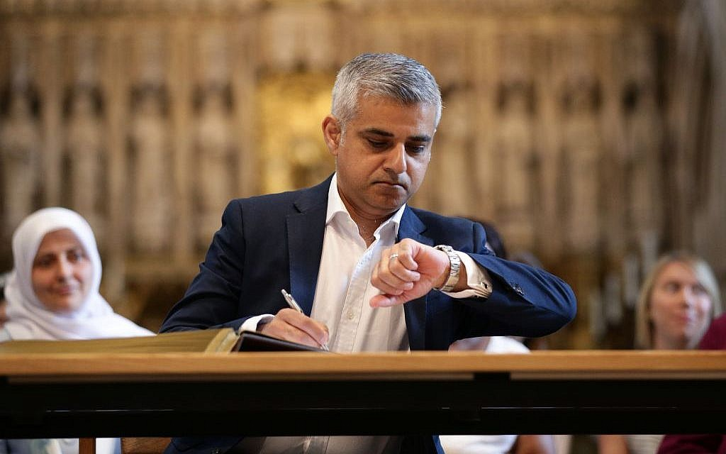 London's new mayor, Sadiq Khan, looks at his watch during the official signing ceremony in Southwark Cathedral, London, Saturday May 7, 2016. (Yui Mok/Pool via AP)