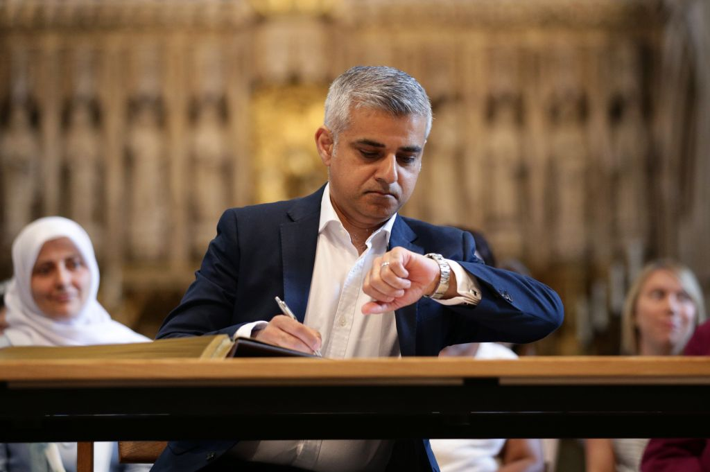 London's new mayor, Sadiq Khan, looks at his watch during the official signing ceremony in Southwark Cathedral, London, Saturday May 7, 2016. On Friday the 45-year-old Labour Party politician became the first person of Islamic faith to lead Europe's largest city. (Yui Mok/Pool via AP)