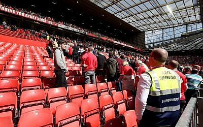 Fans leave the stands after a security announcement during the English Premier League match at Old Trafford, Manchester, England, May 15, 2016. (Martin Rickett/PA via AP)