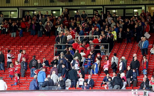 Fans and players leave the pitch and North and West stands after an announcement to evacuate before the English Premier League match at Old Trafford, Manchester, England. The match was later abandoned after a suspect package was found in the stadium. Sunday May 15, 2016. Martin Rickett/PA via AP)