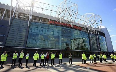 Security guards stand outside Old Trafford stadium after the final soccer match of the season between Manchester United and AFC Bournemouth was abandoned due to a suspect package being found inside the stadium on May 15, 2016. (Mike Egerton/PA via AP)