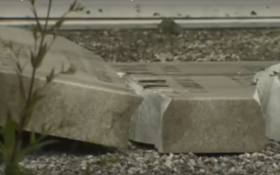 A headstone pushed over by vandals lies broken in Blackley Jewish cemetery (YouTube screenshot)