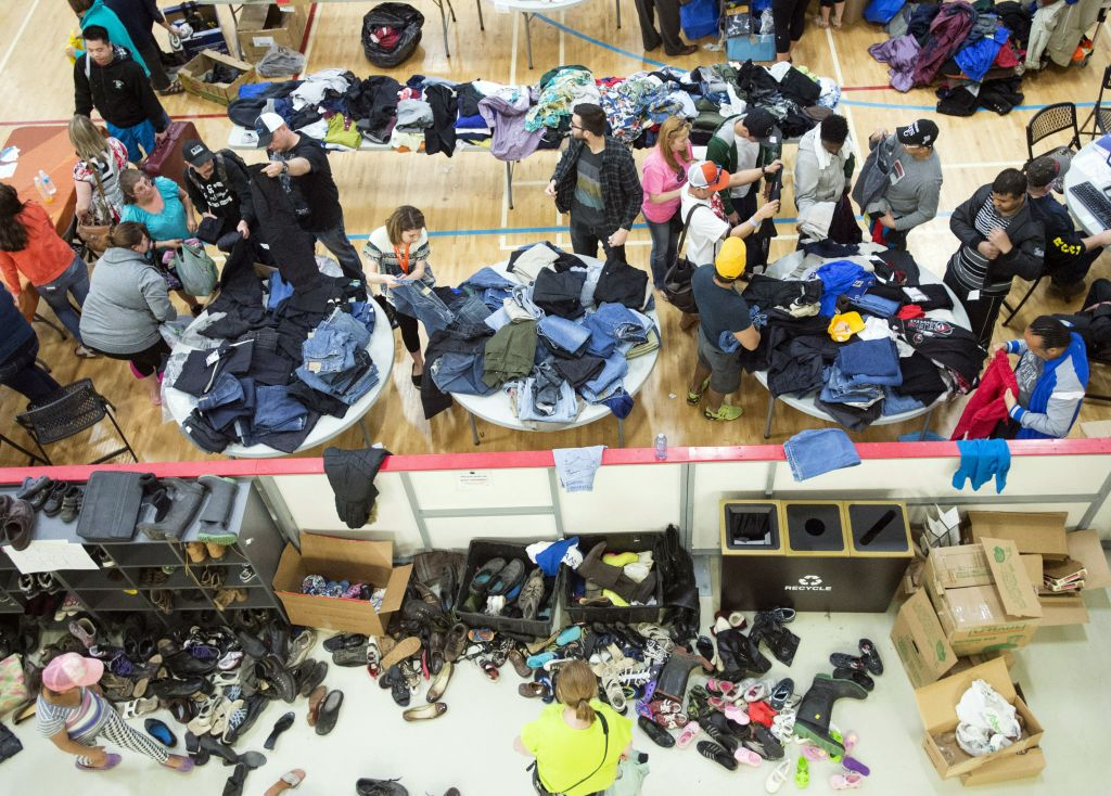 Evacuees from the Fort McMurray wildfires look through donated supplies in Lac la Biche, Alberta, Canada on Friday, May 6, 2016. More than 80,000 people have left Fort McMurray in the heart of Canada' oil sands, where the fire has torched 1,600 homes and other buildings. (Ryan Remiorz/The Canadian Press via AP)