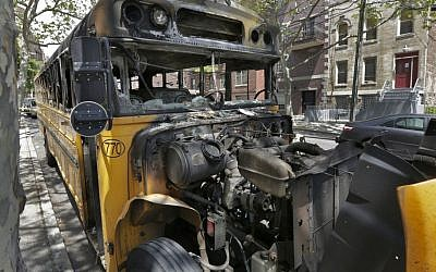 The remains of a school bus that was burned Sunday May 8, 2016, sits on a street in the Crown Heights section of the Brooklyn borough of New York, Wednesday May 11, 2016. (AP/Richard Drew)