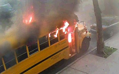 In this frame grab taken from surveillance video, a school bus burns after it was set on fire by children Sunday, May 8, 2016, in the Crown Heights section of the Brooklyn borough of New York. (Beth Rifkah School via AP)