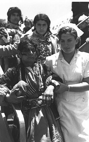 A nurse helps an Iraqi immigrant at Lod Airport, late spring 1951 (Teddy Brauner, GPO)
