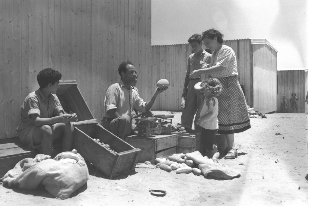 Mrs. Pliska, a new immigrant from Bessarabia (today Moldova/Ukraine) buys vegetables from Eliahu Abraham, a former actor from Baghdad, at the maabara (immigrant camp) in Kiryat Ono, summer 1951 (Teddy Brauner, GPO)