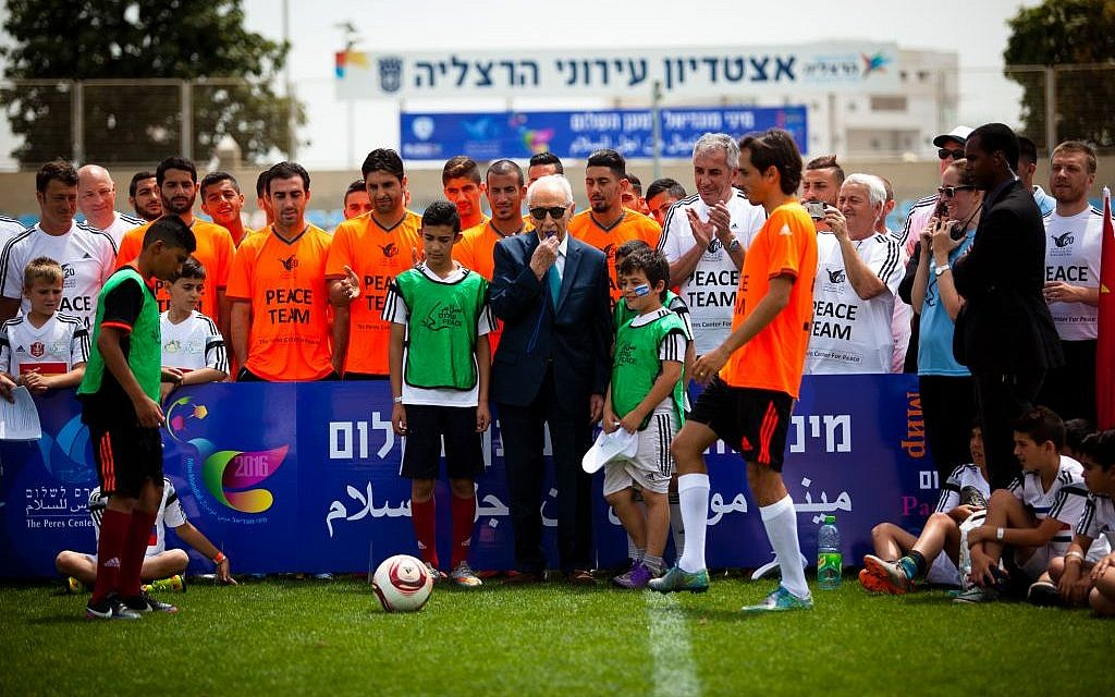 Shimon Peres, in suit, with soccer players and future soccer players at the Peres Center For Peace's Mini Mondial for Peace in Herzliya on May 9, 2016. (Efrat Saar/Courtesy)