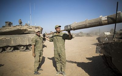 Israeli soldiers clean the barrel of a tank cannon at a deployment area near the border with the Gaza Strip on August 2, 2014. (Yonatan Sindel/Flash90)