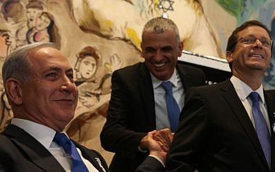 Prime Minister Benjamin Netanyahu (left) shakes hands with leader of the Kulanu party Moshe Kahlon (center) during the opening session of the 20th Knesset on March 31, 2015. At right is Zionist Union leader Isaac Herzog (Nati Shohat/Flash90)