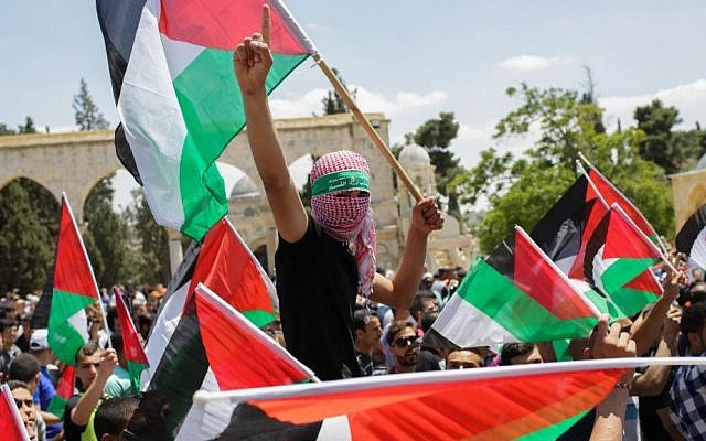 """Palestinians wave their national flag during a demonstration to mark the """"Nakba"""" or """"catastrophe,"""" a reference to the birth of the state of Israel outside the Al-Aqsa mosque in Jerusalem's Old City on May 15, 2015. (Muath Al Khatib/Flash90)"""