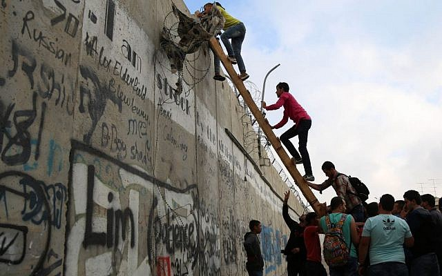 Illustrative: Palestinian men climb a section of Israel's security barrier in the village of Al-Ram, on June 26, 2015 (Flash90)