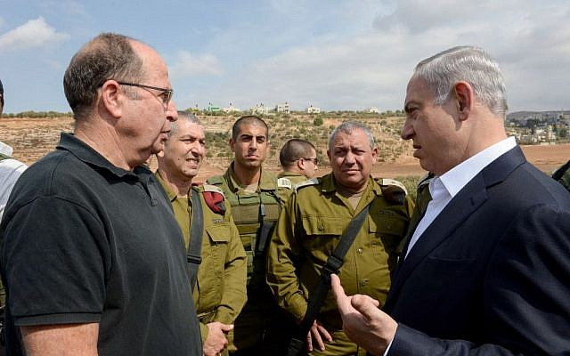 Israeli Prime Minister Benjamin Netanyahu, right, speaks with Defense Minister Moshe Ya'alon on October 6, 2015. (Amos Ben Gershom/GPO)